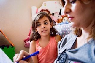Ao lado de Maísa Zakzuk, autora do livro, a menina Mariam, filha de palestinos nascida em Damasco, mas que teve a nacionalidade síria negada pelo país. A família dela vivia num campo de refugiados frequentemente alvo de ataques e bombardeios. Além da prát (Foto: Divulgação)