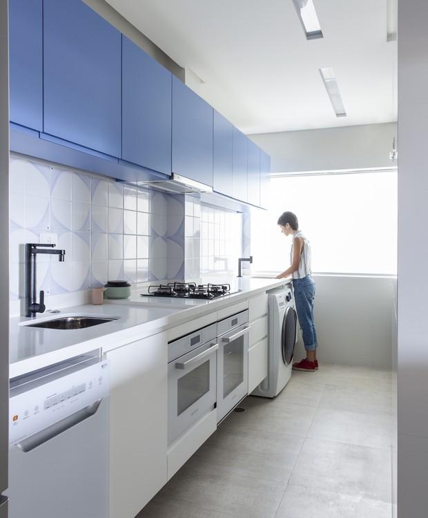 Cozinha e lavanderia estão integradas por uma grande bancada de Silestone que abriga todos os eletrodomésticos. No frontão, azulejos do ateliê Leopardi Esperante (Foto: Maíra Acayaba/Divulgação)