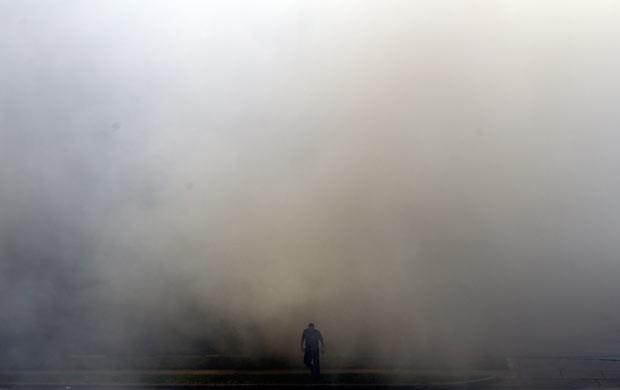 Bombeiro em meio à fumaça do incêndio nesta sexta-feira (31) em Houston, no Texas (Foto: AP Photo/Houston Chronicle, Cody Duff)