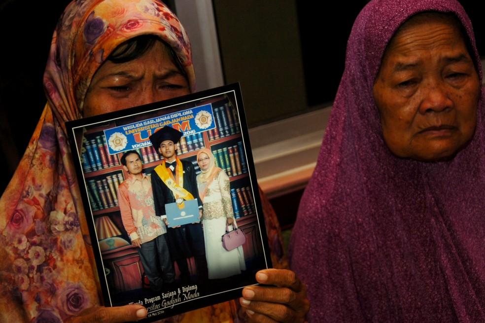 Mãe chora ao mostrar foto de graduação de seu filho, Agil Nugroho Septian, passageiro do avião que caiu na Indonésia em 29 de outubro — Foto: Antara Foto/Lukmansyah via Reuters