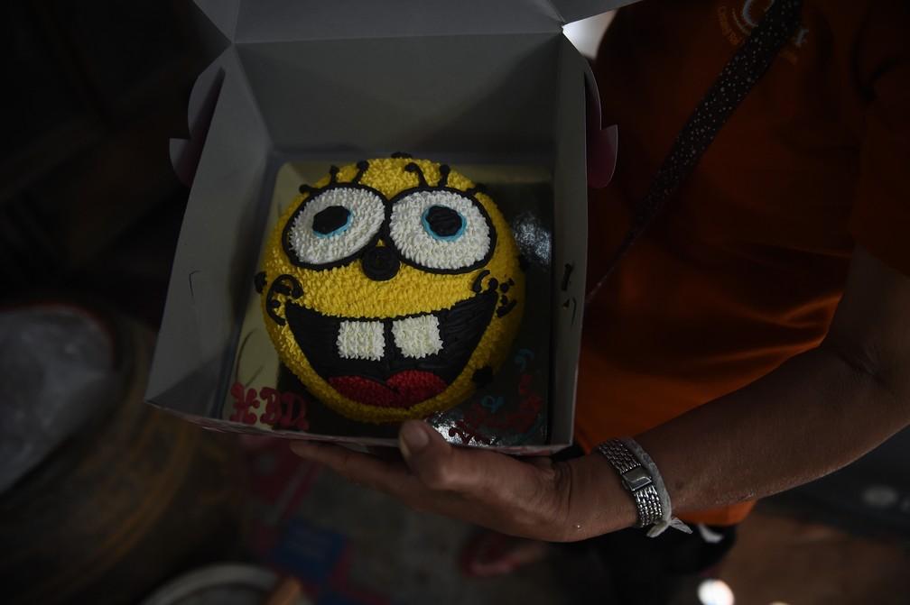 Mãe mostra o bolo de aniversário ainda guardado para rapaz preso em caverna na Tailândia (Foto: Lillian Suwanrumpha / AFP)