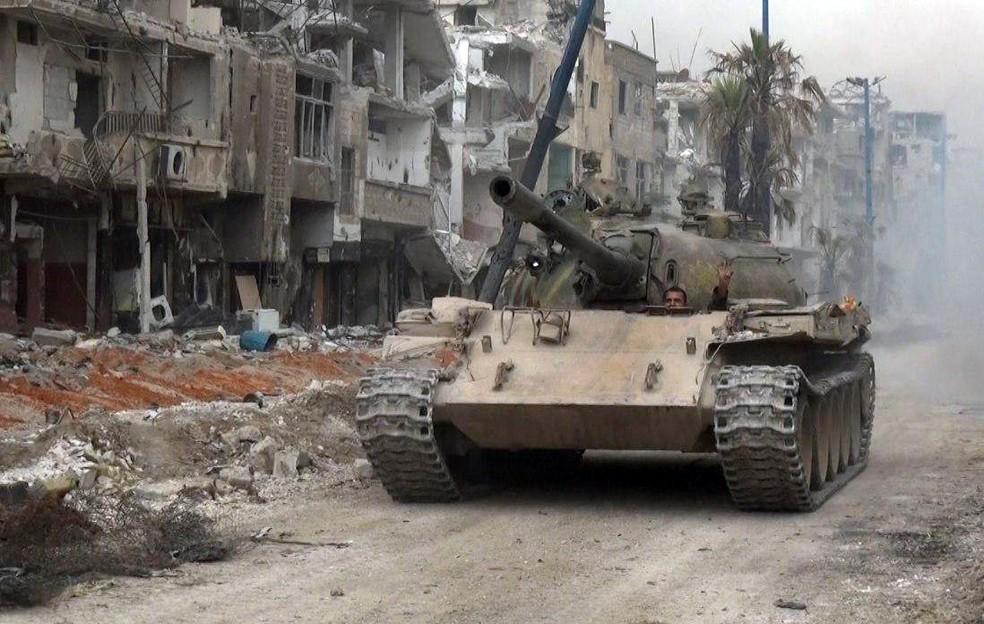 -  Tanque do exército sírio avança em uma rua de Hajar al-Aswad em confronto anterior contra o Estado Islâmico  Foto: AFP/Sana