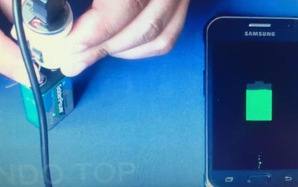 Celular sendo carregado Image caption Momento ideal para conectar celular por meio de cabo USB é quando elétrons estão passando de um polo a outro (Foto: YouTube/Mundo Top)