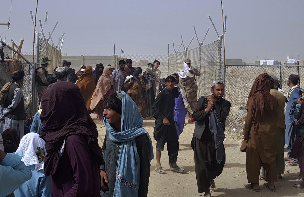 População do Afeganistão atravessa uma barreira de segurança ao cruzar a fronteira, em Chaman, Paquistão. — Foto: ASSOCIATED PRESS