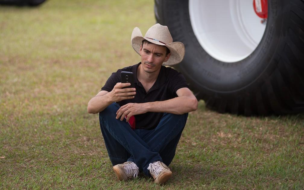 Visitante descansa na sombra do trator em estande na Agrishow 2018 em Ribeirão Preto (Foto: Érico Andrade/G1)
