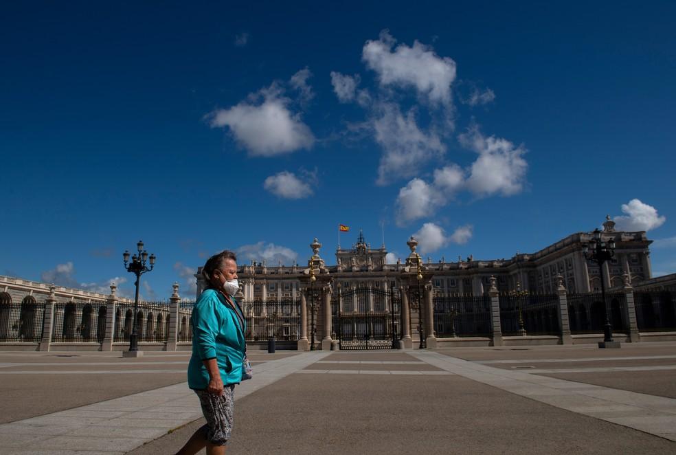 Mulher caminha em frente ao Palácio Real de Madri, na Espanha. — Foto: Pierre-Philippe Marcou/AFP