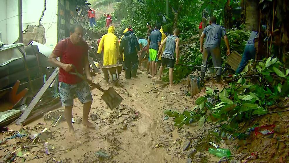 Moradores da área onde família soterrada ajudaram a retirar barro, em Cavaleiro, em Jaboatão, no Grande Recife — Foto: Mattheus Sampaio/ TV Globo