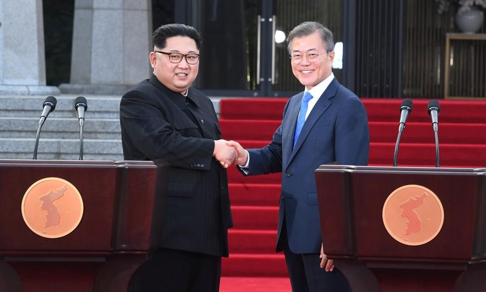 O presidente sul-coreano Moon Jae-in e o líder da Coreia do Norte Kim Jong-un dão um aperto de mão durante encontro em Panmunjom, dentro zona desmilitarizada que separa os dois países — Foto: Korea Summit Press Pool/via Reuters