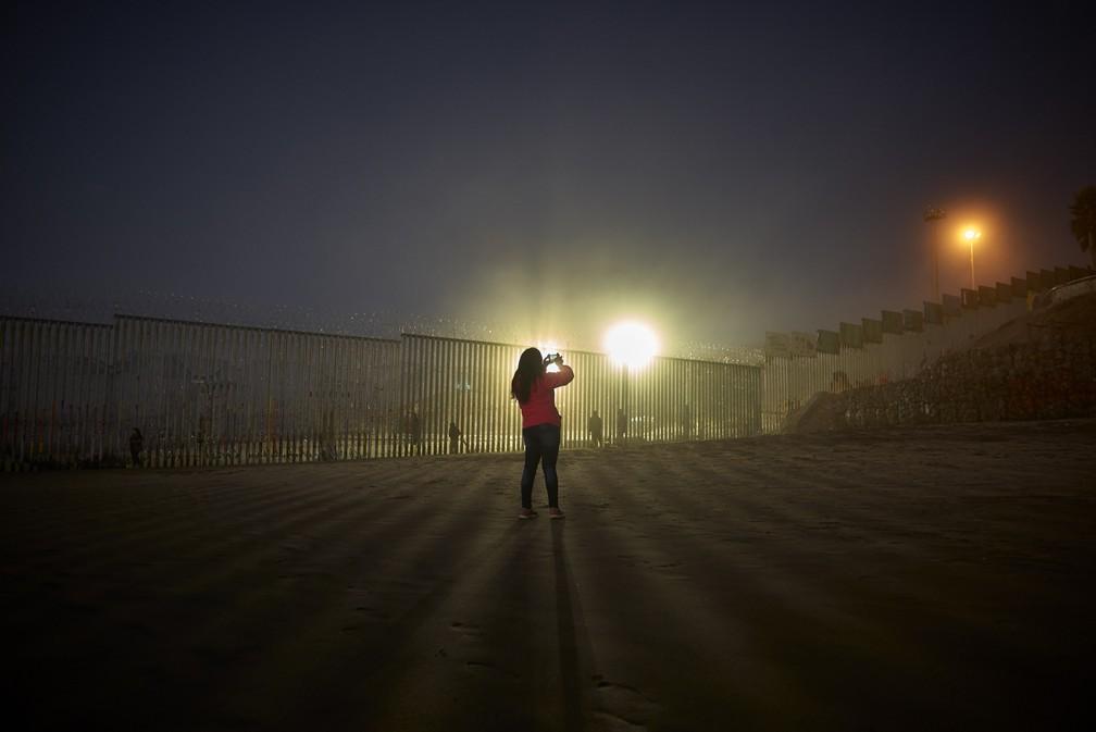 Mulher faz imagens com telefone, enquanto holofotes dos Estados Unidos iluminam a parede com arame farpada na fronteira, ao longo da praia em Tijuana, no México — Foto: AP Photo/Gregory Bull