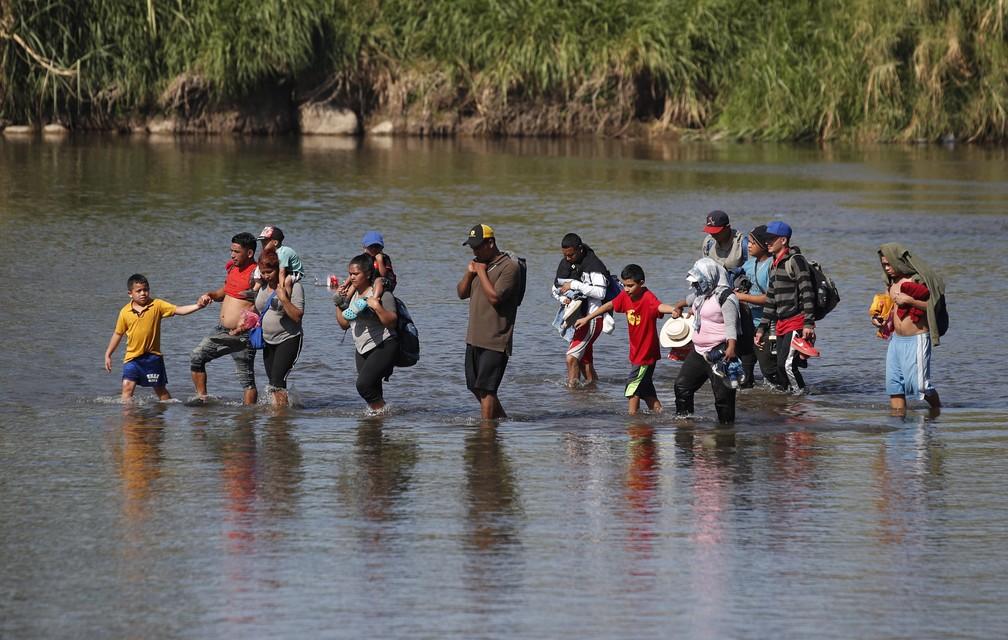 Migrantes cruzam rio a pé para chegar ao México a partir da Guatemala nesta terça-feira (21) — Foto: Moises Castillo/AP Photo