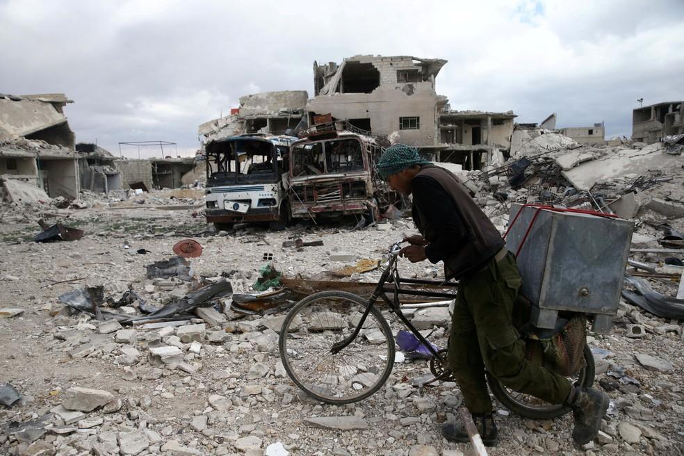 Homem caminha com bicicleta em área de Duma, na Síria, danificada por combates (Foto: Bassam Khabieh/Reuters)