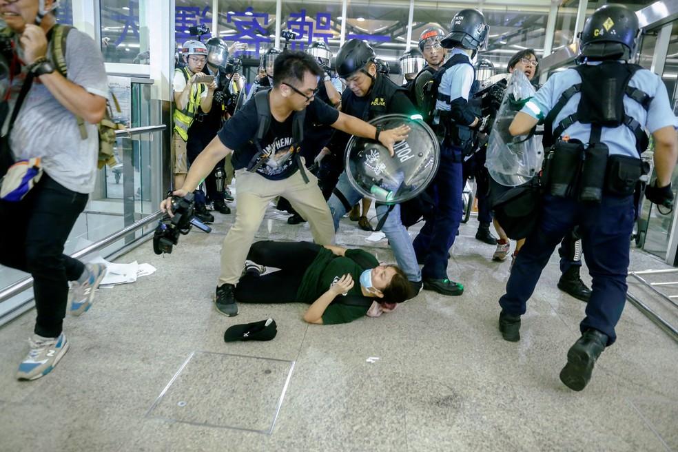 Polícia usa spray de pimenta para dispersar os manifestantes dentro do aeroporto de Hong Kong nesta terça-feira (13). — Foto: Thomas Peter/Reuters