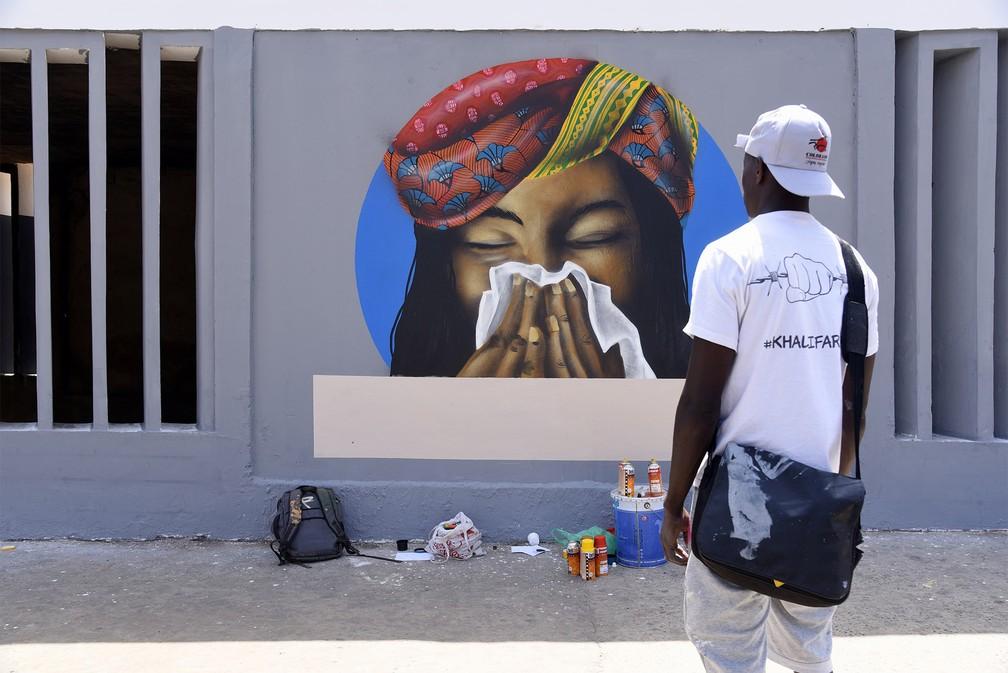 21 de março - Artistas do grupo senegalês de grafite RBS Crew finalizam o desenho de uma mulher cobrindo o nariz com um lenço enquanto espirra, medida recomendada para prevenção contra o coronavírus, em um centro universitário de Dakar, no Senegal — Foto: Seyllou/Reuters