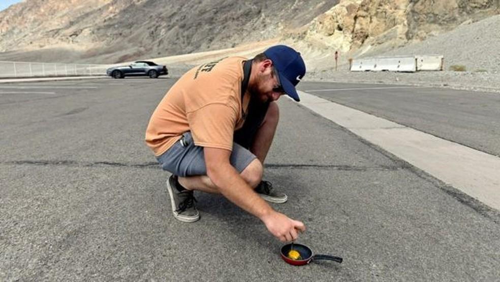 Homem tenta fritar ovo na rua de região considerada muito quente — Foto: Reuters