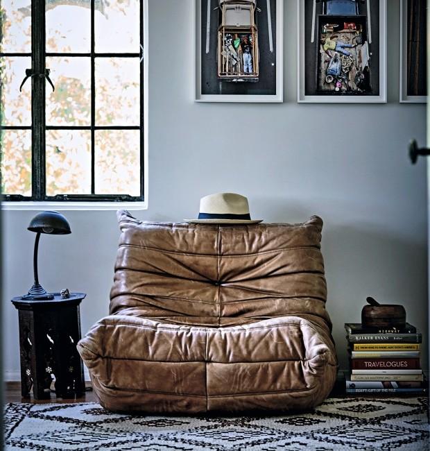 Recanto. Confortável poltrona Togo, de Michel Ducaroy, um clássico do design criado em 1973. Nela, um dos muitos chapéus de Walton. Tapete e mesa lateral orientais (Foto: Martin Lof / Living Inside)