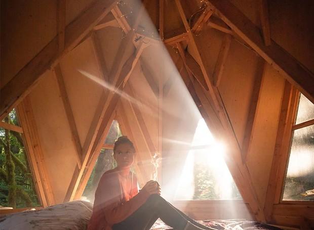 A luz invade o ambiente pelas janelas triangulares instaladas na parte de cima da casa. Já ao entardecer, os moradores podem observar o céu estrelado da floresta (Foto: Instagram/ Reprodução)
