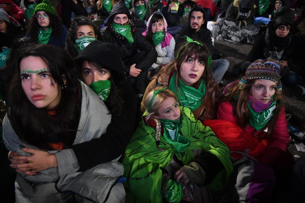 Ativistas pró-aborto aguardavam em frente à Assembleia Nacional, durante a madrugada desta quinta-feira (14), a votação do projeto de lei que legaliza a prática do aborto na Argentina   (Foto: Eitan Abramovich / AFP)