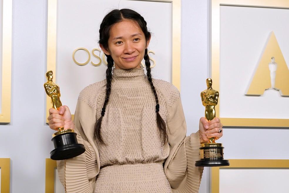 """Chloé Zhao, diretora de """"Nomadland"""", posa com os dois Oscars que venceu neste domingo (25) — Foto: Chris Pizzello/Pool via REUTERS"""