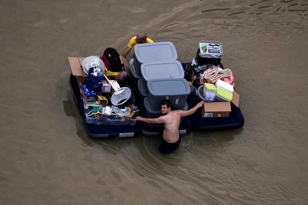 Foto tirada em 31 de agosto de 2017 - Homem protege seus pertences em uma rua inundada após passagem do furacão Harvey em Houston, nos EUA — Foto: Adrees Latif/Reuters