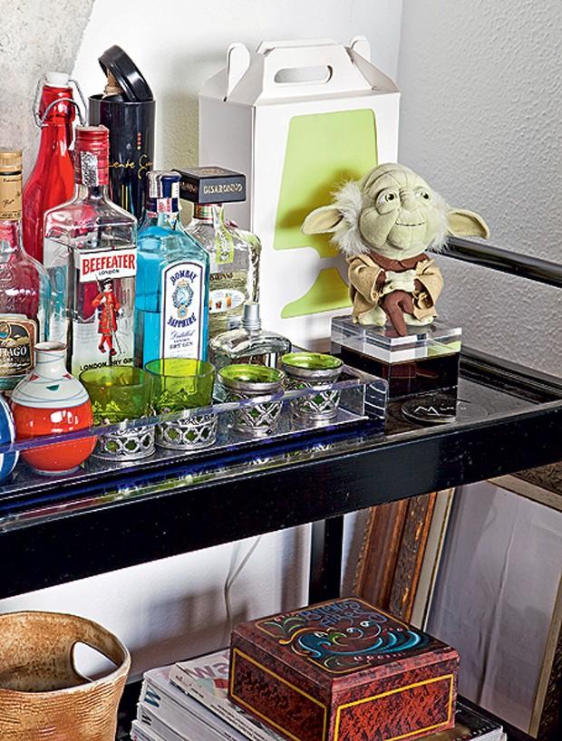 Com função de bar, o carrinho de chá do fotógrafo Lufe Gomes foi presente da designer Monica Cintra. As bebidas ficam ao lado de um boneco divertido do mestre Yoda, do filme Guerra nas Estrelas (Foto: Lufe Gomes e Victor Affaro/Casa e Jardim)
