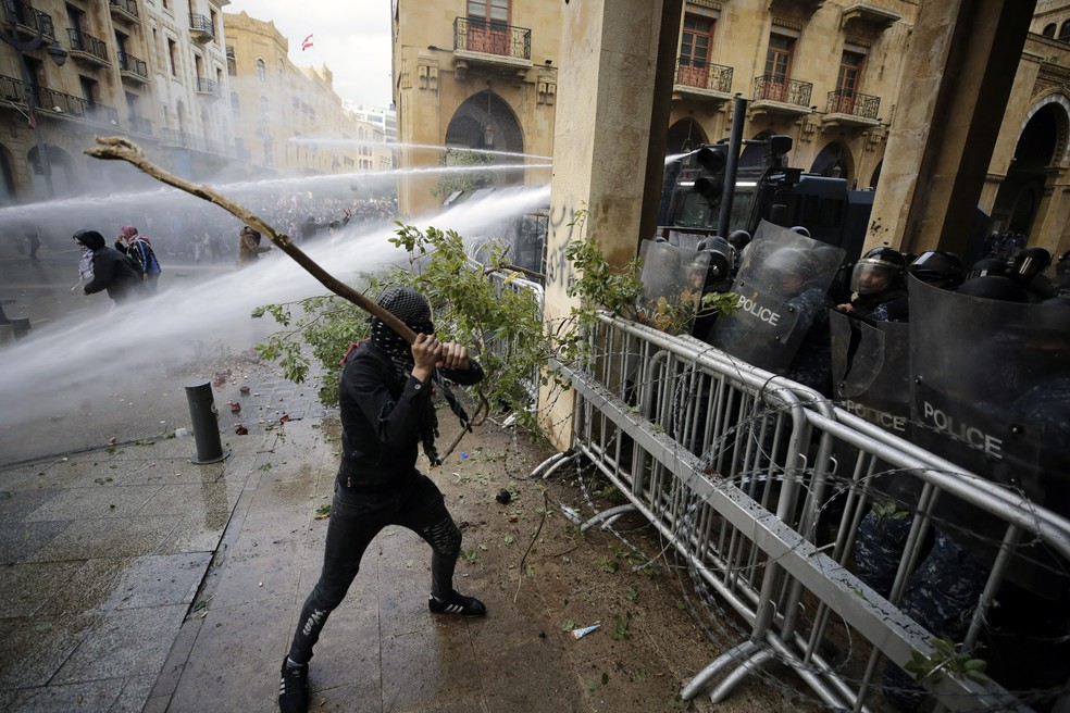 Manifestante em Beirute, no Líbano, usa galho de árvore contra cerco policial, que revida com jatos d'água, durante protesto neste sábado (18) — Foto: Hassan Ammar/AP Photo