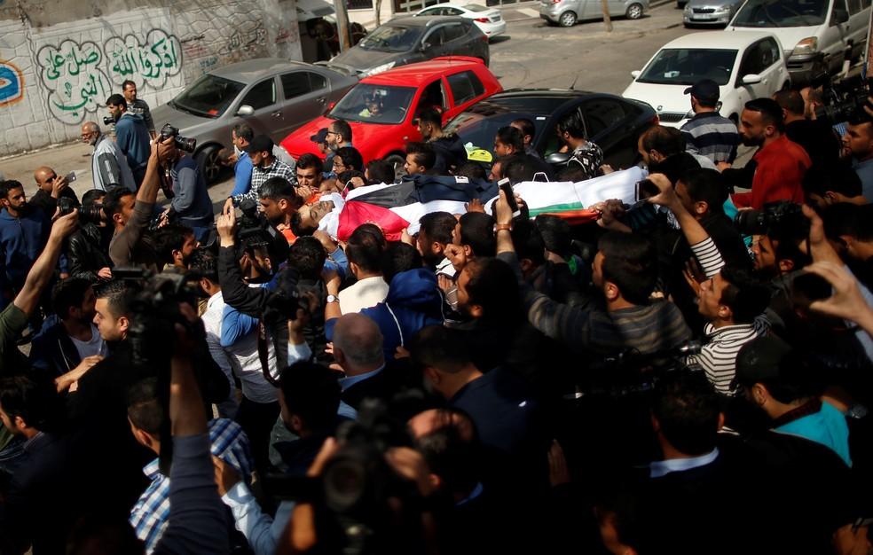 Colegas do jornalista Yasser Murtaja, morto no conflito, carregam seu corpo durante funeral em Gaza. (Foto: Suhaib Salem/Reuters)