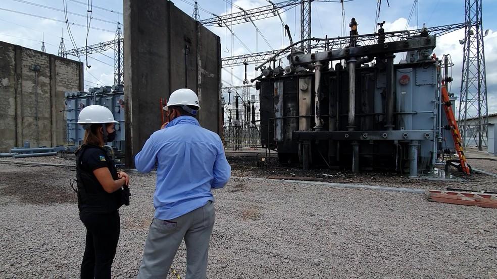 Inspeção na subestação com transformador incendiado ao fundo — Foto: Polícia Civil/Divugação