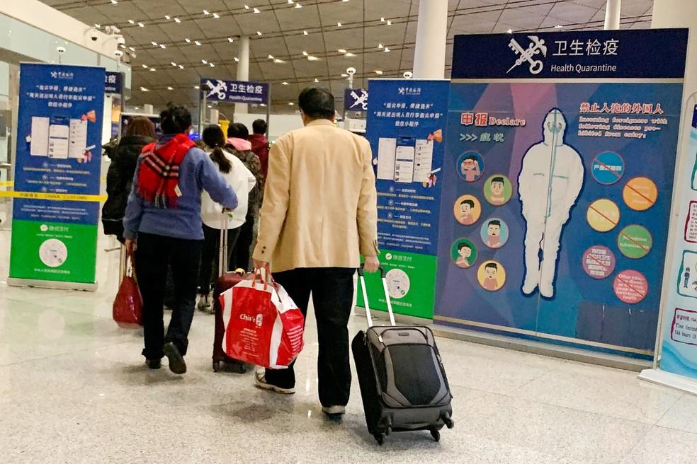 Passageiros passam por um controle de saúde na imigração do aeroporto internacional de Pequim, na China, na segunda-feira (13) — Foto: Ng Han Guan/AP