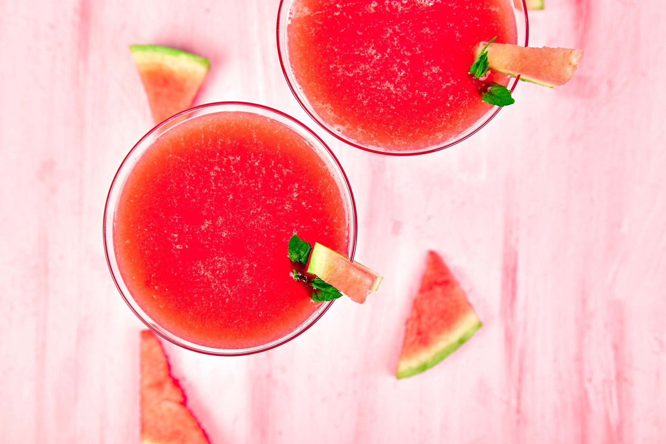 Watermelon margarita cocktail on pink background. Fresh watermelon lemonade with mint and  ice for summer party. Refreshing summer drink. Top view. (Foto: Getty Images/iStockphoto)