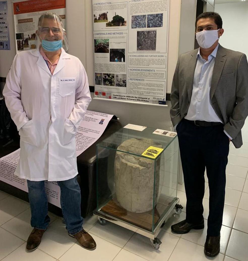 Sandro Marden e Alysson Medeiros em foto juntos com o barril de cimento encontrado durante a pesquisa — Foto: Divulgação/UFPB