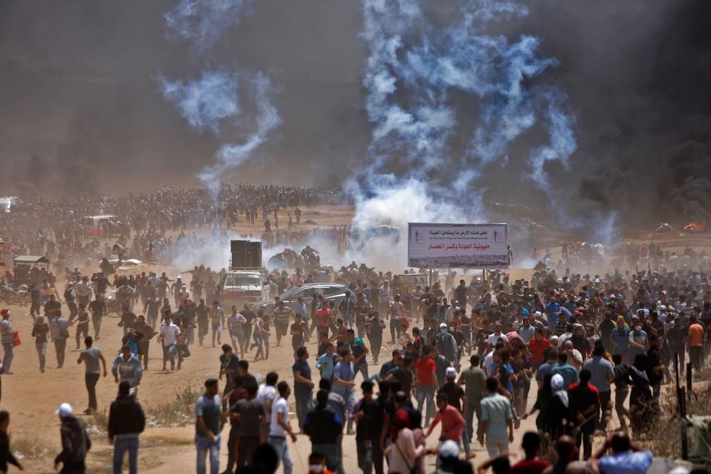Palestinos correm para se proteger de bombas de gás atiradas por tropas israelenses na fronteira entre Gaza e Israel após protestos contra a inauguração da embaixada dos EUA em Jerusalém (Foto: Mohammed Abed/AFP)