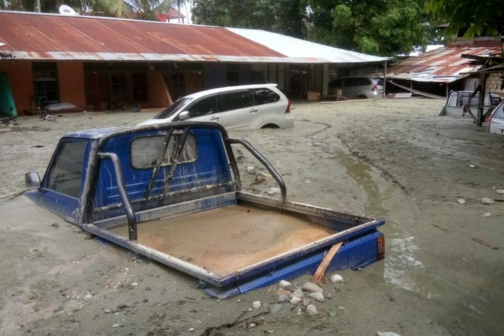 Carro submerso em inundação na Papua, na Indonésia — Foto: Gusti Tanati/Antara Foto via Reuters