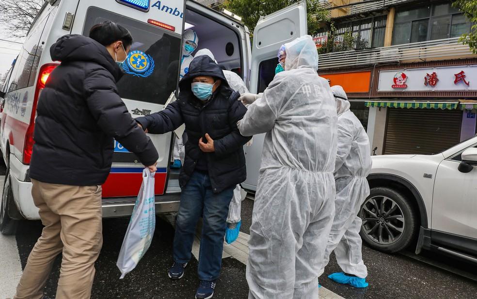 Médicos ajudam paciente a sair de uma ambulância em Euhan, na província de Hubei, na China, no domingo (26) — Foto: Chinatopix via AP