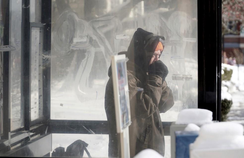 Morador de Pittsfield, Massachusetts, no nordeste dos EUA, se abriga em ponto de ônibus contra onda de frio (Foto: Ben Garver/