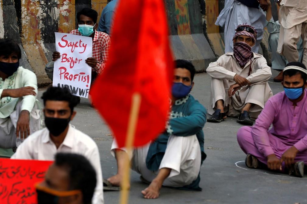Ativistas de várias organizações trabalhistas, usando máscaras protetoras como medida preventiva contra a propagação de coronavírus (COVID-19), participam de um comício exigindo melhorias nas condições de trabalho, durante o Dia Internacional do Trabalho, em Karachi, no Paquistão — Foto: Akhtar Soomro/Reuters