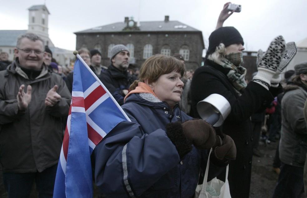 Mulher segrando a bandeira da Islândia é vista durante protesto contra medidas adotadas pelo governo em 2009 (Foto: Ints Kalnins/ Reuters)