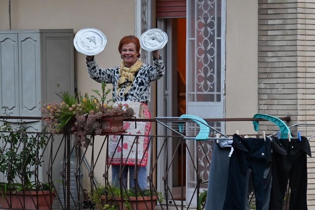 Uma moradora usa tampa de panelas durante um 'flashmob' chamado 'Olhe pela janela, minha Roma!' (Affacciati alla Finestra, Roma Mia!) durante isolamento para evitar a propagação do novo coronavírus em Roma, na Italia, em 13 de março  — Foto:  Andreas Solaro/AFP