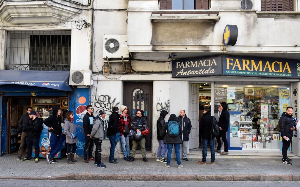 Compradores cadastrados fazem fila para comprar maconha legal em farmácia de Montevidéu, no Uruguai, no primeiro dia de vendas, na quarta (19) (Foto: AP Photo/Matilde Campodonico)