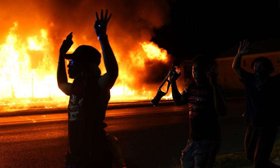 Manifestantes passam com mãos ao alto diante de policiais em Kenosha, no Wisconsin (EUA), após novos protestos contra o racismo e a violência policial terminarem em confronto na noite de segunda-feira (24) — Foto: David Goldman / AP Photo