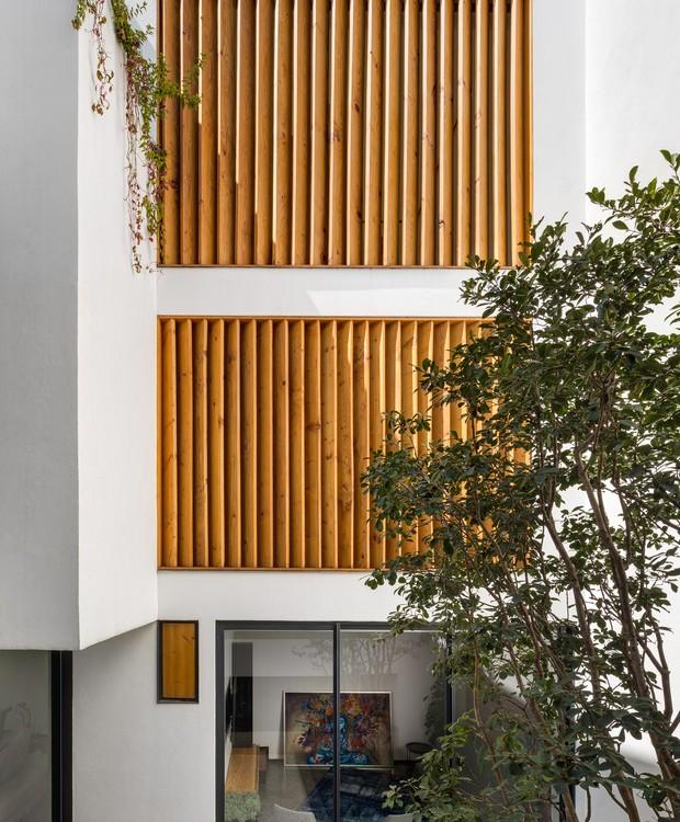 Persianas de madeira aquecem o ambiente de cores frias (Foto:  Rafael Gamo/ Reprodução)