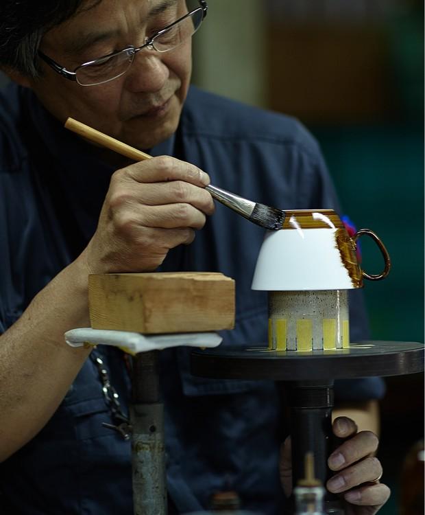 Um esmalte especial, aplicado artesanalmente sobre as xícaras, é o responsável pelo efeito espelhado (Foto: D-Bros/Reprodução)