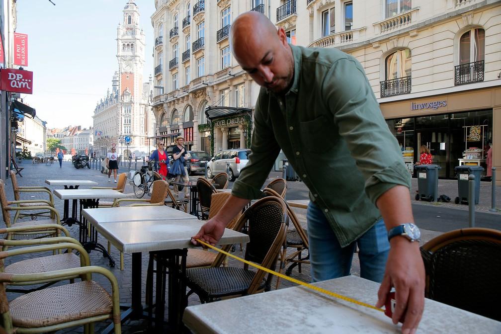Homem mede distância entre mesas em café de Lille, no norte da França, nesta terça-feira (2)  — Foto: Michel Spingler/AP