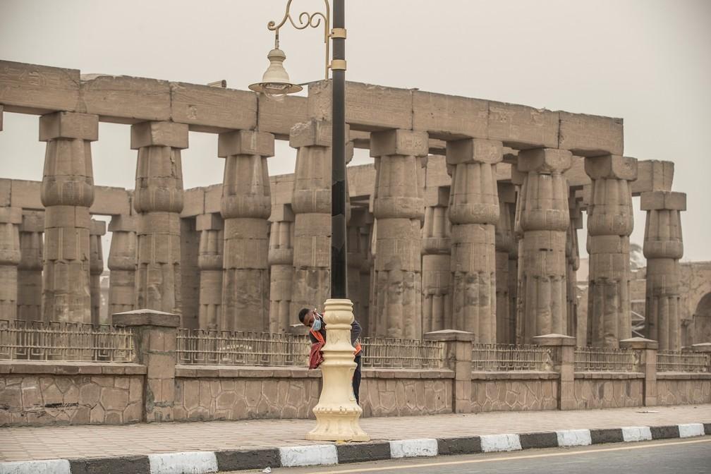 12 de março - Um funcionário da prefeitura limpa postes de luz em meio a uma tempestade de areia e temores de coronavírus perto do Templo de Luxor, no sul do Egito — Foto: Khaled Desouki/AFP