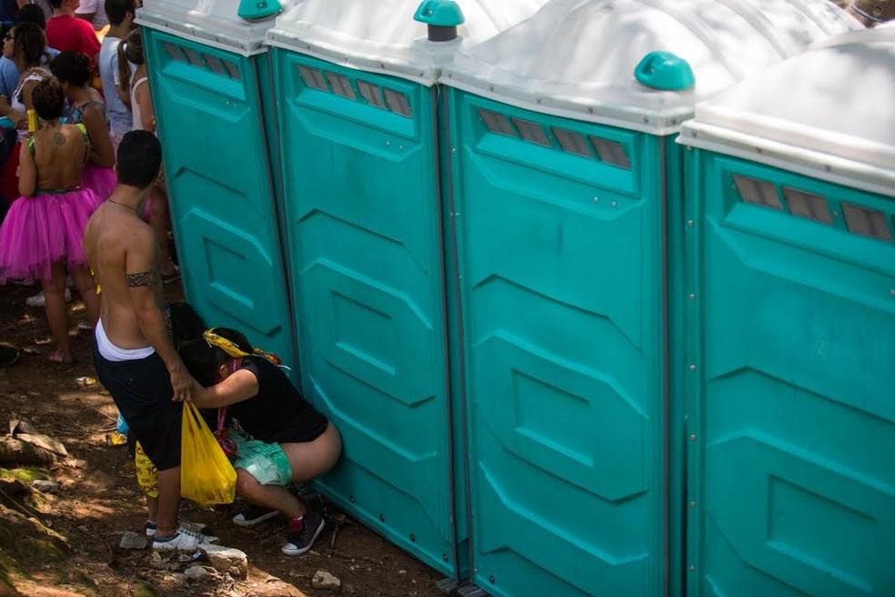 Mulher faz xixi fora dos banheiros químicos (Foto: Victor Moriyama/ G1)