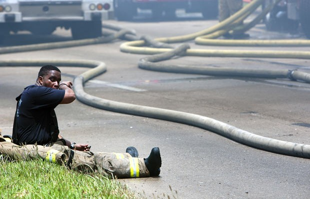 Bombeiro toma fôlego durante combate ao incêndio (Foto: AP Photo/Houston Chronicle, Cody Duff)