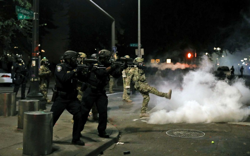 Policial federal chuta uma lata de gás lacrimogêneo durante manifestação em Portland — Foto: Caitlin Ochs / Reuters