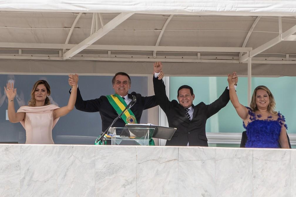 Jair Bolsonaro e Hamilton Mourão erguem os braços com suas mulheres no Parlatório, diante do público que assiste  a cerimônia — Foto: Fábio Tito/G1