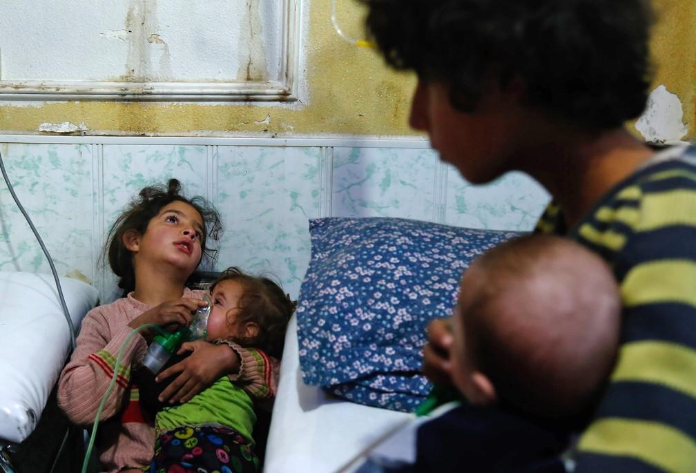 Crianças colocal máscara de oxigêncio em bebês após relato de ataque químico em Guta Oriental, na Síria (Foto: Hasan Mohamed/AFP)
