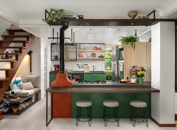 A cozinha foi ampliada com o deslocamento da bancada e integrada à sala de jantar e estar. A estante suspensa guarda abriga livros e objetos decorativos (Foto: Rafael Ribeiro/Divulgação)