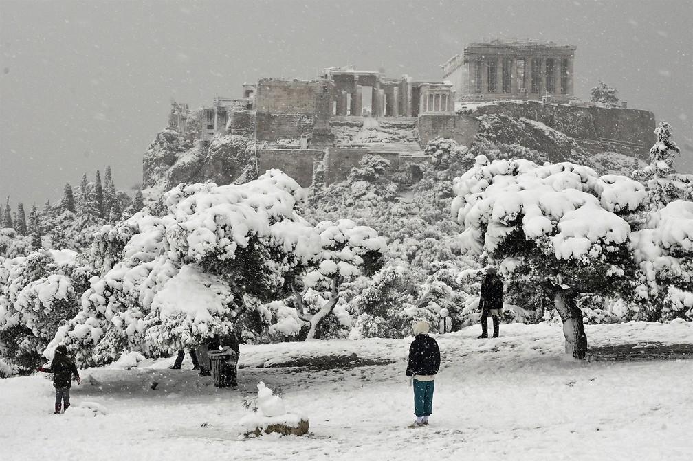 Pessoas observam de longe a Acrópole coberta de neve, em cena rara provocada por forte nevasca em Atenas, na Grécia — Foto: Louisa Gouliamaki/AFP